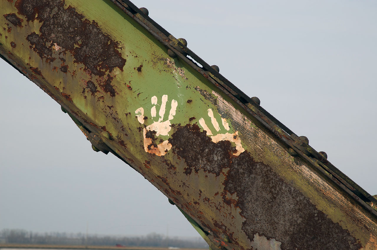 Prints of hands on rusted steel girder
