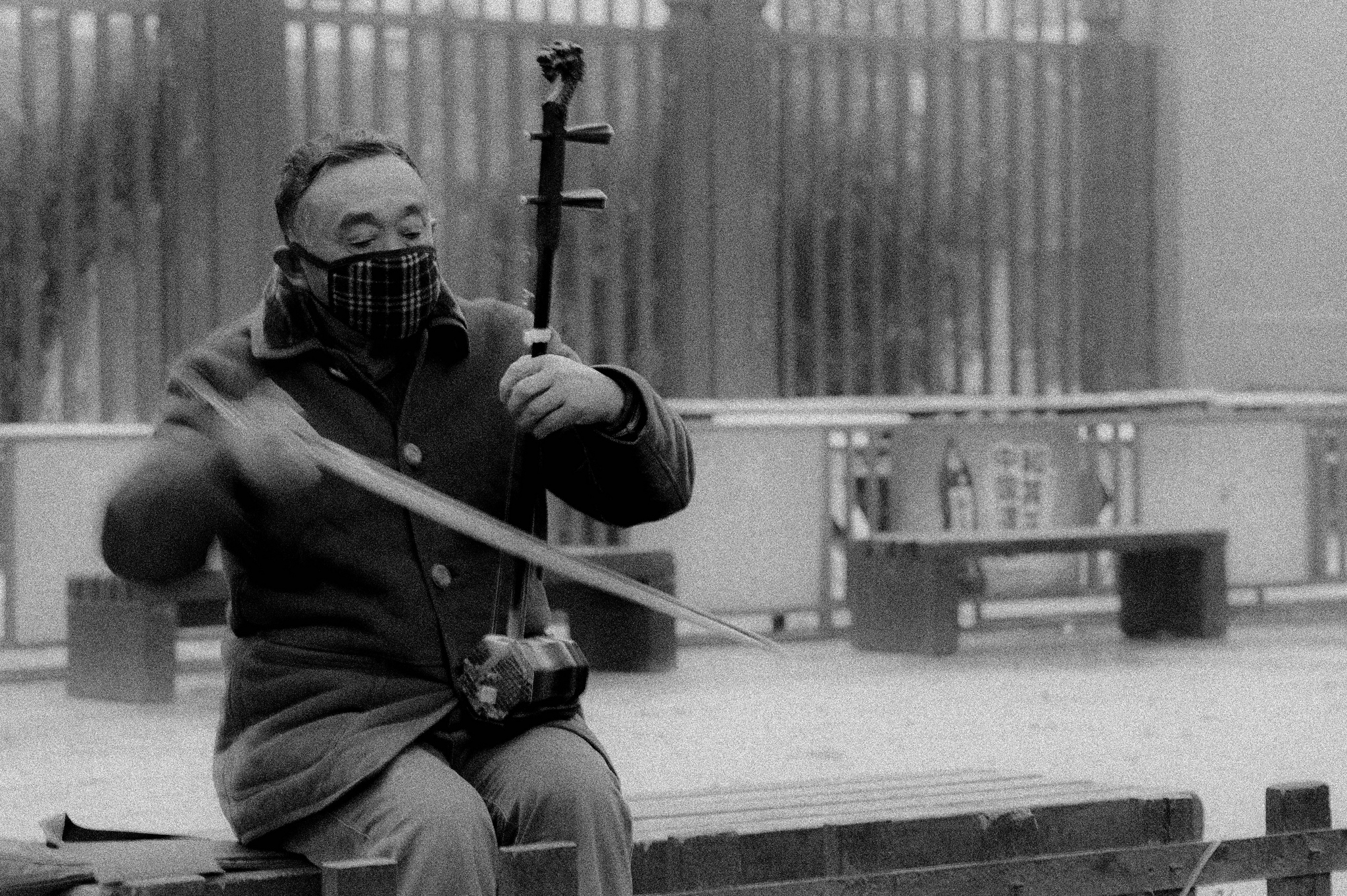 Musician playing in empty Beijing square, mouth and nose covered to protect against the pollution
