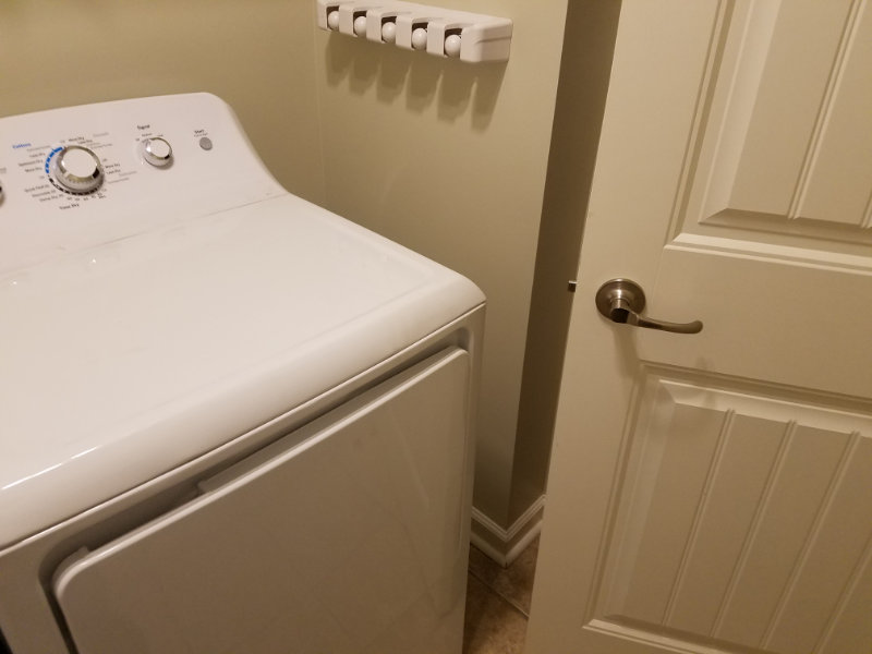 Showing dryer with barely any clearance for door into laundry room